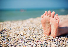 Female feet on white shell beach Royalty Free Stock Photos