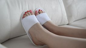 Female feet in white slippers on couch stock video