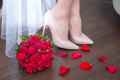 Female feet in white wedding sandals with a bouquet Stock Photo