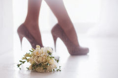 Female feet in white wedding sandals with a bouquet Royalty Free Stock Images