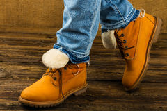 Female feet in winter boots and jeans. On wooden background Stock Photography