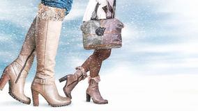 Female feet in winter shoes. Snowfall in the foreground stock photo