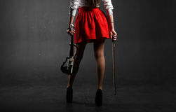 Female feet. A woman in a red skirt with a violin. And fiddlestick Stock Photos