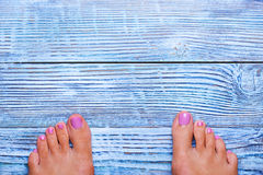 Female feet on wooden background Royalty Free Stock Images