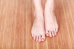 Female feet on wooden floor Stock Images