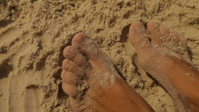 Female feet in the yellow sea sand stock footage