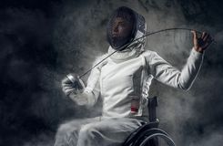 Female paralympic wheelchair fencer. Female fencer in wheelchair with safety mask on a face holding rapier, dust effect on image Royalty Free Stock Image
