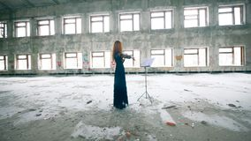 Female fiddler plays violin while standing in abandoned building. 4K stock footage