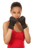 Female fighter. Black fitness model wearing red fitness outfit on white background Stock Images
