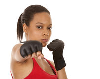Female fighter. Black fitness model wearing red fitness outfit on white background Royalty Free Stock Images