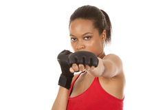 Female fighter. Black fitness model wearing red fitness outfit on white background Stock Image