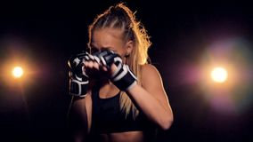 A female fighter practices her punches in fingerless gloves. stock video