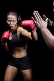 Female fighter hitting on trainer hand Stock Image