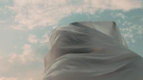 Female Figure Lost Under Plastic Foil At Sunset