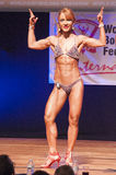 Female figure model flexes her muscles and shows her physique Royalty Free Stock Image