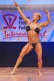 Female figure model flexes her muscles and shows her physique Royalty Free Stock Photos