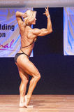 Female figure model flexes her muscles and shows her physique Stock Image