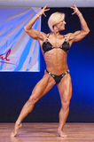 Female figure model flexes her muscles and shows her physique Royalty Free Stock Photo
