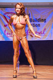 Female figure model shows her best at championship on stage Royalty Free Stock Photography