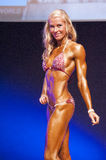 Female figure model shows her best at championship on stage Stock Photos