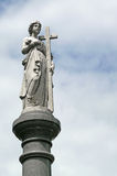 Female figure statue with cross atop tombstone Stock Photography