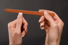 Female filing nails. White female filing nails with nailfile Stock Photography