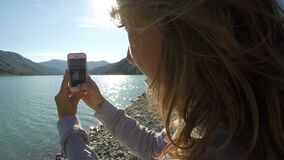 Female filming mountain landscape and river on cell phone on a sunny day. Stock footage stock video