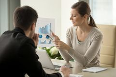 Female financial adviser explaining business plan. Attractive millennial businesswoman presenting company financial indicators, telling business partner about Royalty Free Stock Photo