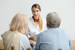 Female financial advisor talking consulting senior aged couple a royalty free stock photography