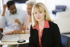 Female Financial Advisor With Couple In Background Stock Image