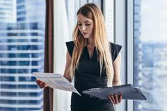 Female financial analyst holding papers studying documents standing against window with city view royalty free stock photos