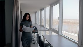 Female financial analytic saleswoman going through office corridor and investgating graphs. Young woman in grey dress holding printed market trends in her stock footage