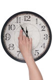 Female finger changes the time on a clock Royalty Free Stock Photos