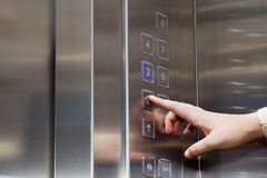 Female finger presses the button for the elevator. Female finger presses the button on the glowing panel elevator Stock Photography