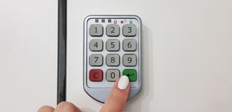 Female finger pushes green enter key on a door of security white locker royalty free stock image