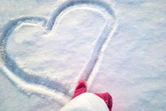 Female Finger in red gloves draws a heart in the snow stock photography