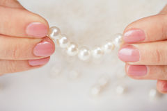 Female fingers hold thread with pearls Royalty Free Stock Image