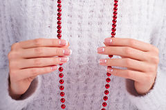 Female fingers holding a red necklace. Stock Photography