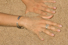 Female fingers  sand beach Stock Photos