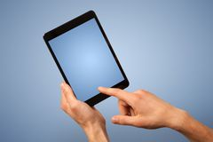 Female hand holding tablet. Female fingers touching blank tablet Royalty Free Stock Photo