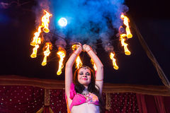 Female Fire Dancer Holding Flaming Apparatus Stock Photo