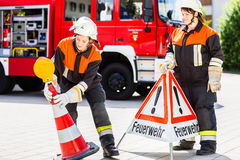 Female fire fighters setting up attention sign Stock Photo