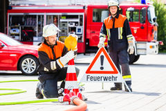 Female fire fighters setting up attention sign. Female fire fighters in emergency operation setting up attention sign Royalty Free Stock Images