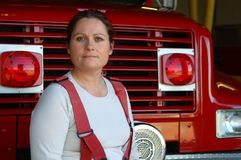 Female Firefighter. Sitting on the front of a fire engine Royalty Free Stock Photography