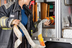 Female Firefighter Adjusting Hose In Truck. Midsection of female firefighter adjusting water hose in truck at fire station royalty free stock image