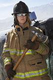 Female Firefighter Holding Axe. Portrait of a female firefighter holding axe by crashed car stock photos