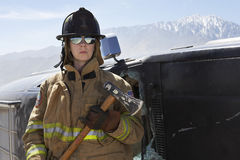 Female Firefighter Holding Axe. By a crashed car royalty free stock images