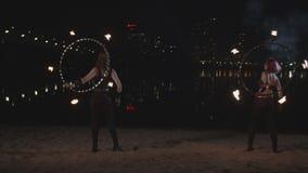 Lovely firegirls juggling fire hoops on riverside stock video footage