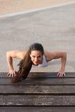 Female fitness athlete doing push ups workout Royalty Free Stock Image