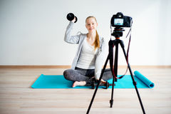 Female fitness blogger. Doing exercises at home Royalty Free Stock Photo